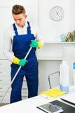Męski fachowy janitor okurzanie w biurze fotografia stock