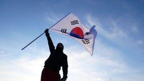 Męski fan z Poludniowo-koreańską flaga raduje się atlety i wspiera zbiory wideo