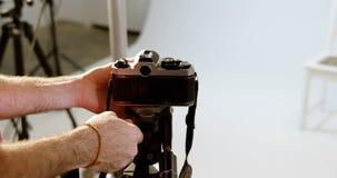 Męski fotograf przystosowywa kamerę w fotografii studiu 4k zbiory wideo