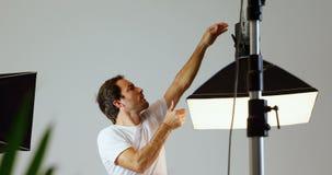 Męski fotograf przystosowywa stroboskop lekki 4k zdjęcie wideo