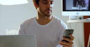 Męski fotograf używa telefon komórkowego podczas gdy pracujący na laptopie 4k zbiory