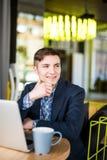 Męski freelancer łączy radio przez laptopu, rozważna biznesmen praca na książce podczas gdy siedzący przy drewnianym stołem Zdjęcie Royalty Free
