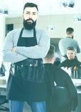 Męski fryzjer pokazuje jego narzędzia i miejsce pracy przy włosianym salonem Fotografia Stock