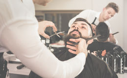 Męski fryzjer precyzyjnie ciie brodę klient Zdjęcie Stock