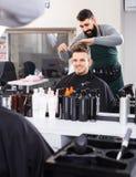 Męski fryzjer robi ostrzyżeniu dla męskiego klienta przy włosianym salonem Fotografia Stock