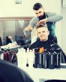 Męski fryzjer robi ostrzyżeniu dla męskiego klienta przy włosianym salonem Zdjęcie Stock