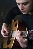 Męski gitarzysta bawić się na gitarze akustycznej Obrazy Royalty Free