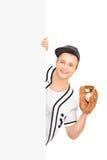 Męski gracz baseballa trzyma piłkę za panelem Zdjęcia Stock