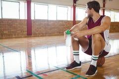 Męski gracz koszykówki patrzeje oddalony podczas gdy siedzący na koszykówce Obraz Stock