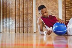 Męski gracz koszykówki używa telefon komórkowego Obraz Royalty Free