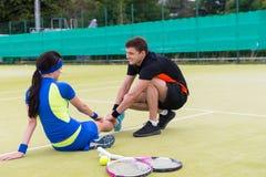 Męski gracz w tenisa masowania kobiety ` s ranił nogę po dopasowania Zdjęcie Royalty Free