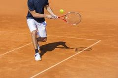Męski gracz w tenisa w akci na glinianym sądzie obraz stock