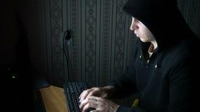 Męski hacker pracuje na komputerze w ciemnym biurowym pokoju zbiory