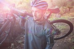 Męski halny rowerzysty przewożenia bicykl w lesie Fotografia Royalty Free