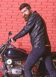 Męski hobby pojęcie Mężczyzna z brodą, rowerzysta w skórzanej kurtki blisko silnika rowerze w garażu, ściana z cegieł tło obrazy stock