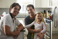 Męski homoseksualny pary obsiadanie z ich córką w kuchni Fotografia Stock