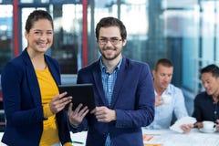 Męski i żeński dyrektor wykonawczy trzyma cyfrową pastylkę Zdjęcie Royalty Free