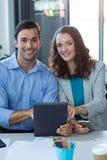 Męski i żeński dyrektor wykonawczy używa cyfrową pastylkę Zdjęcia Stock