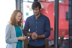 Męski i żeński dyrektor wykonawczy używa telefon komórkowego Obraz Stock