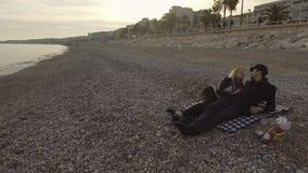 Męski i żeński lying on the beach na koc nadmorski w Ładnym, całujący, romantyczny wieczór zbiory