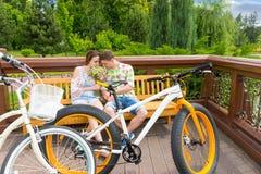 Męski i żeński obsiadanie na ławce i wąchać kwitniemy Fotografia Stock