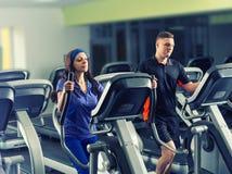 Męski i kobieto ćwiczy na crosstrainer maszynach Zdjęcie Stock