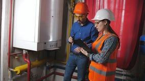Męski inżynier i żeński checker sprawdzamy operability wyposażenie w kotłowym pokoju Kobieta wchodzić do dane w zbiory wideo