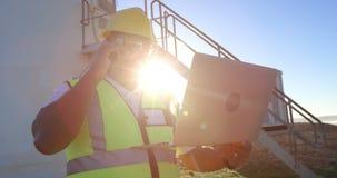 Męski inżynier opowiada na telefonie komórkowym podczas gdy używać laptop 4k zdjęcie wideo