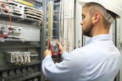 Męski inżynier sprawdza instalację elektryczną z elektronicznymi narzędziami obraz stock