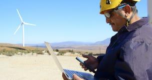 Męski inżynier używa telefon komórkowego podczas gdy pracujący na laptopie 4k zbiory wideo