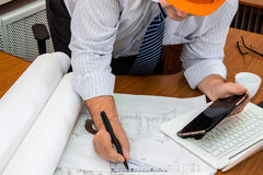 Męski inżynier w hełmie pracuje z projektem Zdjęcie Stock