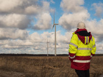 Męski inżynier wewnątrz w zbawczej kurtce i białym hełmie przy polem z planami buduje wiatraczki, Obrazy Royalty Free