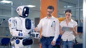 Męski inżynier wyłacza robot dalej, reguluje swój ręki i instruuje żeńskiego inżyniera, zbiory