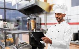 M?ski indyjski szef kuchni z pastylka komputerem osobistym przy kebabu sklepem obrazy royalty free