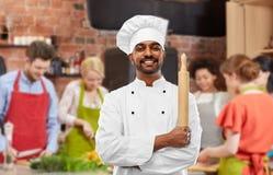 Męski indyjski szef kuchni z wałkownicą przy kulinarną klasą fotografia royalty free