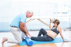 Męski instruktor masuje stopę kobieta w ciąży Fotografia Stock