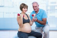 Męski instruktora nauczania kobieta w ciąży ćwiczyć Zdjęcie Royalty Free