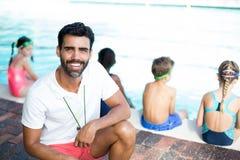 Męski instruktora przycupnięcie dziećmi przy poolside Obraz Stock