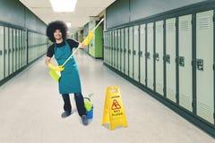 Męski janitor bawić się miotłę w szkole Zdjęcie Royalty Free