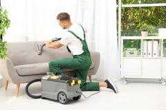 Męski janitor usuwa brud od kanapy fotografia stock