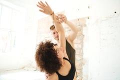 Męski joga instruktor pomaga afro amerykańskiej kobiety Fotografia Stock