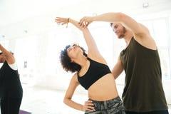 Męski joga instruktor pomaga kobiety robić joga rozciągliwość Obraz Royalty Free