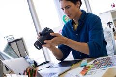 Męski kierownictwo przegląda chwytającą fotografię przy jego biurkiem Zdjęcie Stock