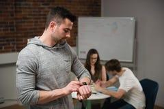 Męski kierownictwo przystosowywa mądrze zegarek podczas gdy kolega dyskutuje w tle Obrazy Royalty Free