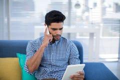 Męski kierownictwo używa cyfrową pastylkę podczas gdy opowiadający na telefonie komórkowym Obraz Stock
