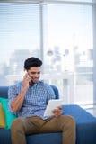 Męski kierownictwo używa cyfrową pastylkę podczas gdy opowiadający na telefonie komórkowym Obrazy Stock