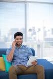 Męski kierownictwo używa cyfrową pastylkę podczas gdy opowiadający na telefonie komórkowym Zdjęcia Royalty Free