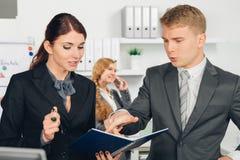 Męski kierownik instruuje żeńskiego pracownika w biurze Zdjęcie Stock