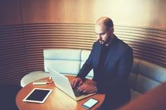 Męski kierownik siedzi w biurowym wnętrzu przy stołem z ciężką przejażdżką, telefonem komórkowym i cyfrową pastylką, Obraz Royalty Free