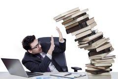 Męski kierownik z spada książkami na biurku Obraz Royalty Free